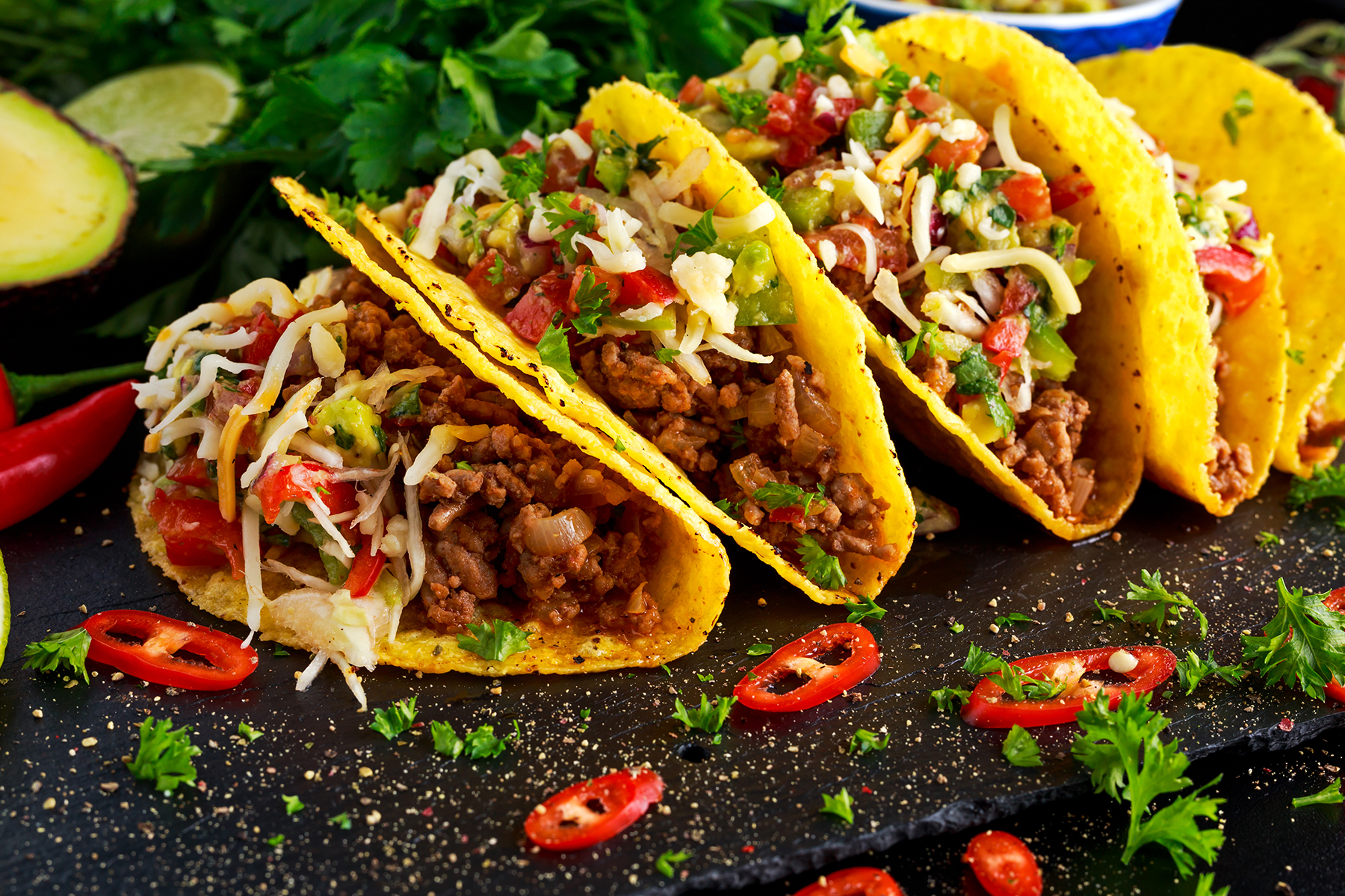 Four Scrumptous Tacos Lined up with ingredients around them