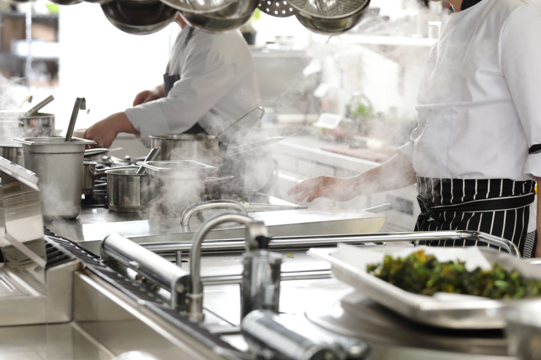Chefs working in steaming stainless steel kitchen