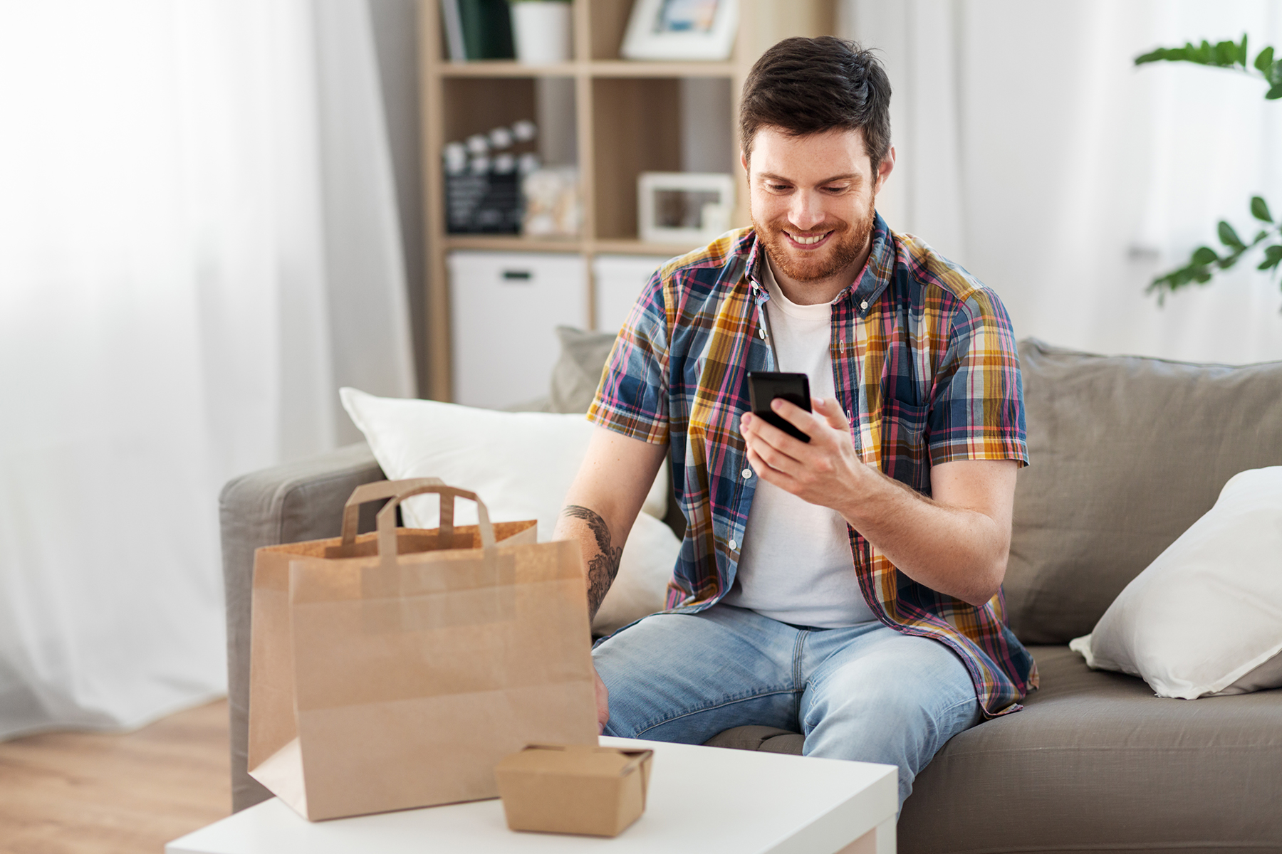 Guy looking at food ordering app after food is delivered