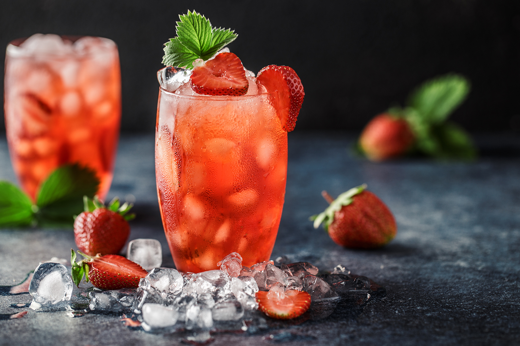 Iced Strawberry Cocktail on table with ice and strawberries next to it