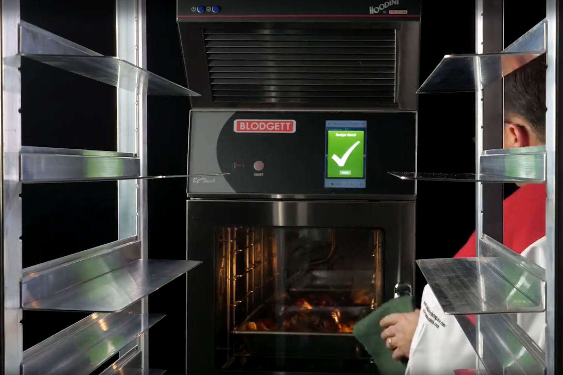 Interior of commercial combi oven with chef opening the oven door
