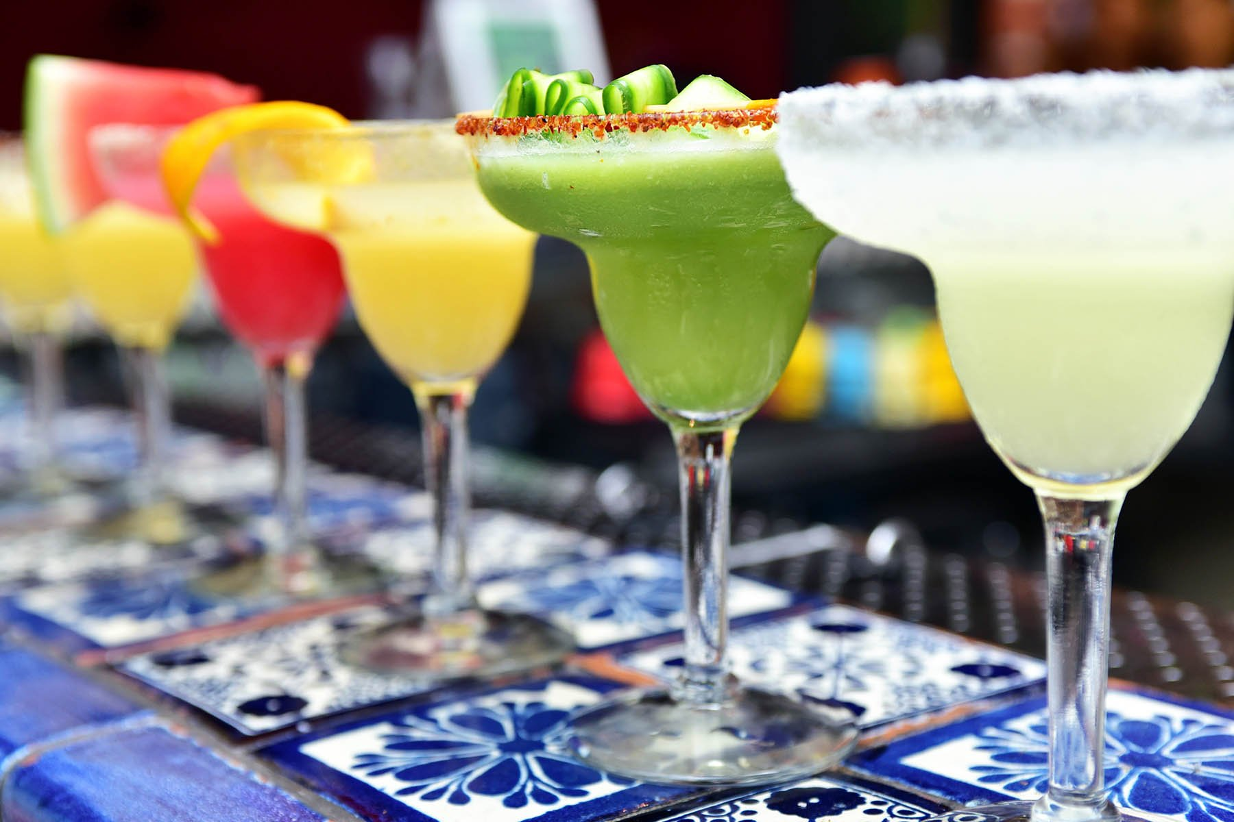 A row of frozen margaritas in cocktail glasses on a bar