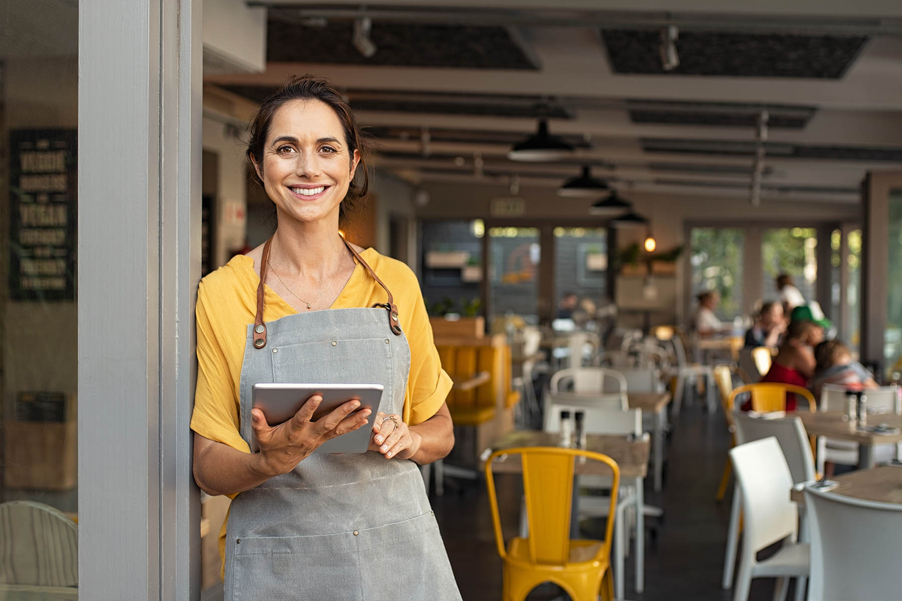 restaurant owner smiling at the camera in front of the restaurant holding a tablet in her hand