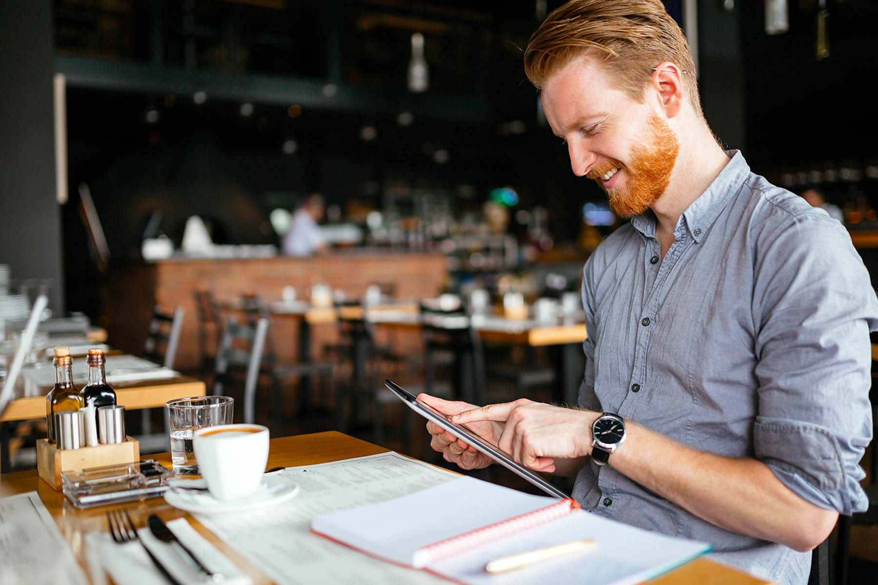 Restaurant owner reviewing information on tablet while sitting at a table at his restuarant